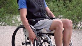 Primo piano lento di giovane uomo disabile dello studente in una sedia a rotelle video d archivio