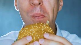 Primo piano mangiatore di uomini un hamburger Alimenti a rapida preparazione Cheeseburger, hamburger, panino archivi video