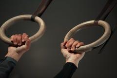 Primo piano - mani maschii sugli anelli di ginnastica Immagini Stock Libere da Diritti