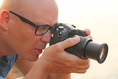 Primo piano maschio del fotografo Il fotografo esamina la lente immagine stock