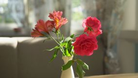 Primo piano Mazzo sveglio delle rose rosse e della fresia in un vaso su una tavola un giorno di estate soleggiato in un caff? immagini stock libere da diritti