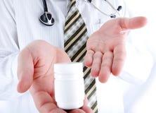 Primo piano, medico che tiene la piccola bottiglia di pillole Fotografia Stock