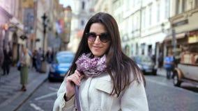 Primo piano medio della ragazza casuale sorridente in occhiali da sole che posano nella città circondata da paesaggio urbano archivi video