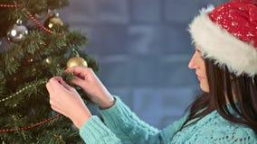 Primo piano medio di bella giovane donna che decora l'albero di Natale che appende palla rossa sul ramo archivi video