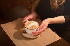 Primo piano nelle mani del caffè di una ragazza che tiene una tazza di caffè con un modello in caffetterie, nel caffè fotografie stock libere da diritti