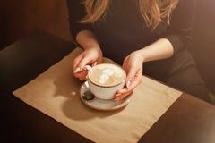 Primo piano nelle mani del caffè di una ragazza che tiene una tazza di caffè con un modello immagine stock