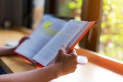 primo piano per i giovani studenti della mano che leggono un libro in caffè del caffè; Immagine Stock