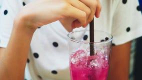Primo piano ragazza in un caffè che beve un cocktail attraverso una paglia Bevande, la gente e stile di vita stock footage