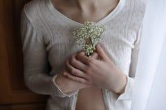 Primo piano ragazza in una blusa d'annata bianca che tiene il piccolo gypsophila bianco dei fiori annata di concetto Fotografie Stock Libere da Diritti