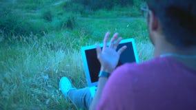 Primo piano, riflessione nello schermo del computer portatile, maschio indiano che parla emozionalmente sul computer portatile di video d archivio