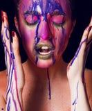 Primo piano ritratto creativo di una ragazza versata con pittura multicolore fotografia stock libera da diritti