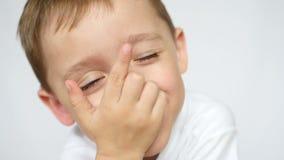 Primo piano: ritratto di un bambino allegro Il ragazzo ride e chiude la sua bocca con la sua mano video d archivio
