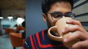 Primo piano, smartphone di sorveglianza del tipo indiano e caffè bevente archivi video