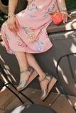 Primo piano sparato dei piedi eleganti di una femmina che porta un vestito con un succo della fragola dal lato fotografia stock
