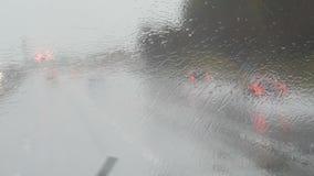 Primo piano sparato delle gocce di pioggia e delle strisce sul bus commovente del od della finestra dalla strada principale nell' archivi video