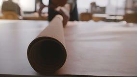 Primo piano sparato delle mani maschii dell'artigiano che spandono un grande pezzo del rotolo di cuoio sulla grande tavola fabbri