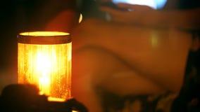 Primo piano sparato di bella candela sulla tavola della barra del salotto di notte, donna con le gambe attraversate facendo uso d video d archivio