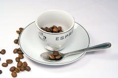 Primo piano stretto della tazza e del piattino del caffè espresso con i fagioli fotografia stock