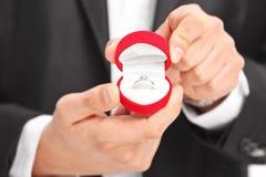 Primo piano su un uomo che tiene un anello di fidanzamento Fotografia Stock Libera da Diritti