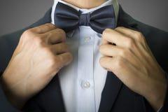 Primo piano su un uomo con un farfallino e un vestito dei blu navy Immagini Stock Libere da Diritti