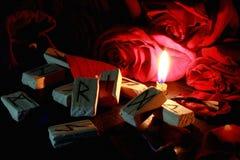 Primo piano su una candela bruciante, sulle rune di legno e sui petali delle rose rosse Dietro le candele è un mazzo di grandi ro immagini stock