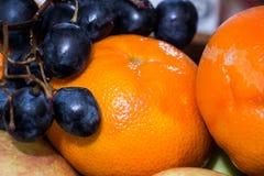 Primo piano succoso dei mandarini con l'uva Fotografia Stock