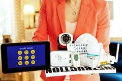 Primo piano sui dispositivi e sul PC domestici astuti della compressa in mani della donna immagine stock