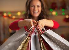 Primo piano sui sacchetti della spesa a disposizione della donna sorridente Fotografia Stock