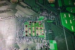 Primo piano sul bordo elettronico nell'officina riparazioni dell'hardware, vaga e tonificata Immagini Stock