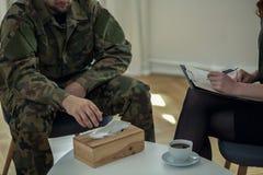 Primo piano sul gridare soldato che raggiunge per un tessuto durante la consultazione con il terapista immagini stock
