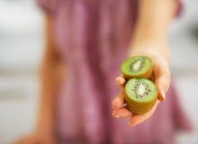Primo piano sul kiwi affettato a disposizione della donna immagine stock libera da diritti