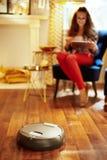 Primo piano sul pavimento di pulizia di vuoto del robot mentre rilassamento della donna immagine stock