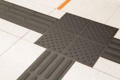 Primo piano sul percorso di pavimentazione tattile dell'interno del piede per i ciechi fotografie stock