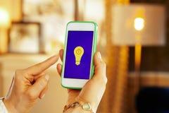 Primo piano sul telefono con le lampade di controllo del app domestico astuto fotografie stock