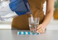 Primo piano sull'acqua di versamento della casalinga in vetro fotografia stock libera da diritti