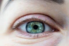 Primo piano sull'occhio aperto di verde della giovane donna fotografie stock