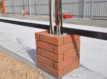 Primo piano sulla costruzione del recinto nuovo Column con il lavoro di muratura, i cavi leggeri e la sbarra di ferro Immagini Stock Libere da Diritti