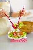 Primo piano sulla donna che mette insalata nel piatto Fotografia Stock Libera da Diritti