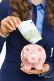 Primo piano sulla donna che mette la banconota dell'euro 100 nel porcellino salvadanaio Fotografie Stock