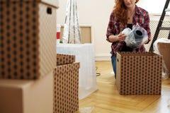 Primo piano sulla donna che protegge il vaso con stagnola mentre imballando nelle scatole fotografie stock libere da diritti