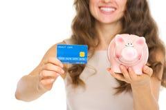 Primo piano sulla donna con la carta di credito ed il porcellino salvadanaio Fotografia Stock