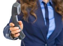 Primo piano sulla donna di affari che dà il microtelefono del telefono immagine stock libera da diritti