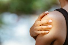 Primo piano sulla donna di forma fisica che ha dolore in spalla immagine stock libera da diritti