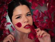 Primo piano sulla donna sensuale attraente che si rilassa nel bagno della stazione termale con il fondo dei petali rosa del fiore immagini stock
