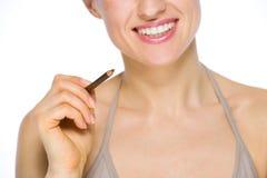 Primo piano sulla donna sorridente che tiene eye-liner marrone Fotografie Stock Libere da Diritti