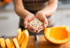 Primo piano sulla giovane casalinga che mostra i semi di zucca Immagini Stock Libere da Diritti