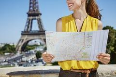 Primo piano sulla giovane donna felice con la mappa a Parigi, Francia fotografia stock