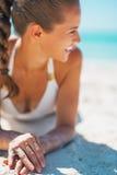 Primo piano sulla giovane donna sorridente in costume da bagno che mette su spiaggia immagine stock
