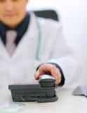 Primo piano sulla mano dei medici che cattura il microtelefono del telefono fotografia stock