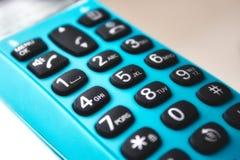 Primo piano sulla tastiera di un telefono tenuto in mano immagine stock